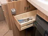 There's a narrow cutlery drawer between the oven and fridge, with a cupboard beneath for storing the detachable drainer in the Swift Esprit 494's kitchen