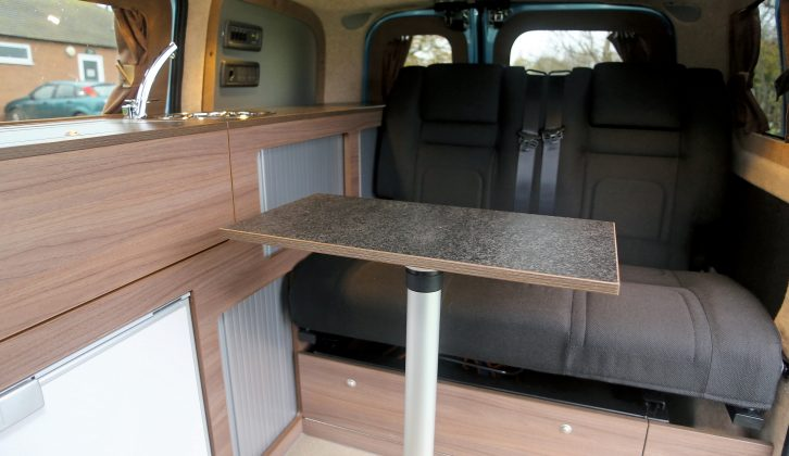 This versatile living space is a lounge-dining-kitchen area, with room for three to eat at the table if you rotate the passenger cab seat in Hillside Leisure's Dalbury E electric campervan, based on the Nissan e-NV200 Combi Acenta