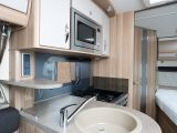 The plinth for the circular sink stands proud from the side of the 'van, and neatly divides the kitchen from the lounge area.