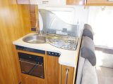 The L-shaped kitchen offers very little worktop area. Some space is redeemed with the glass lid to the sink and hob, and there is an oven in the Dethleffs Esprit T7150 DBM motorhome