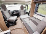The front dinette offers an occasional berth, by using a grey infill cushion to plug the gap between the travel seat bench and driver's seat