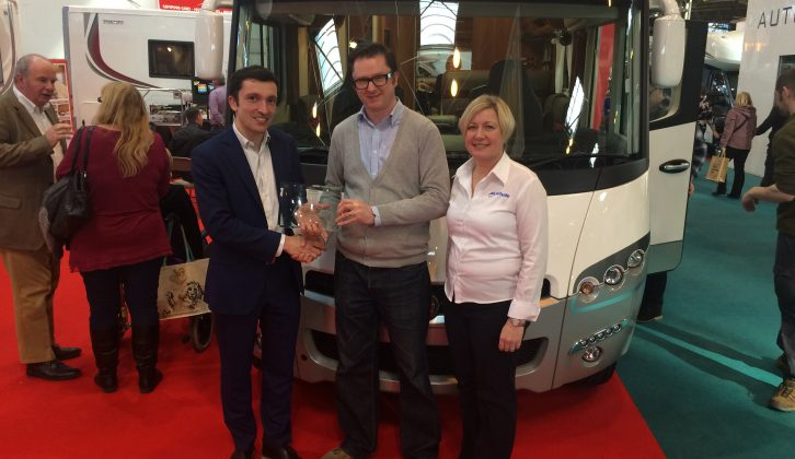 Alex Hacques, Export Sales Executive of Rapido Motorhomes, accepts the trophy for highest-scoring manufacturer of pre-owned motorcaravans in the Practical Motorhome Owner Satisfaction Awards 2016 from Editor Niall Hampton and Sarah Baird, RV Business Development Manager of awards sponsors Whale