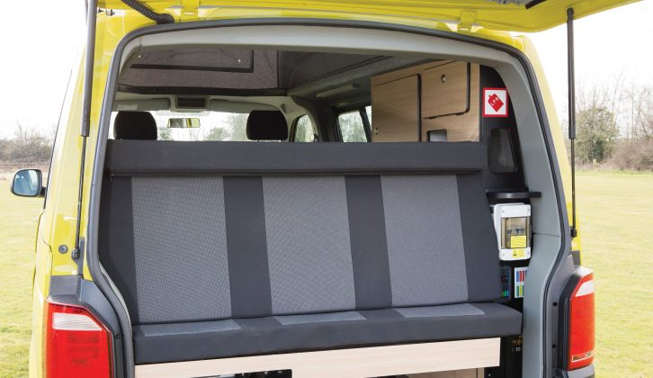 The rear seat assembly is fixed in one position, but there's storage space under it and on a ledge behind the backrest ledge