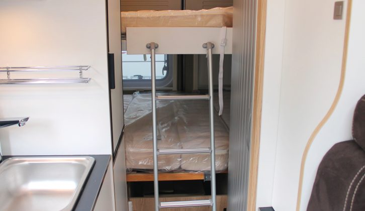 The spacious upper bunk is accessed via a ladder, which sits beside the washroom's tambour door