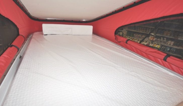 Upper bed is the wider of the two, and has a one-piece mattress on plastic springing
