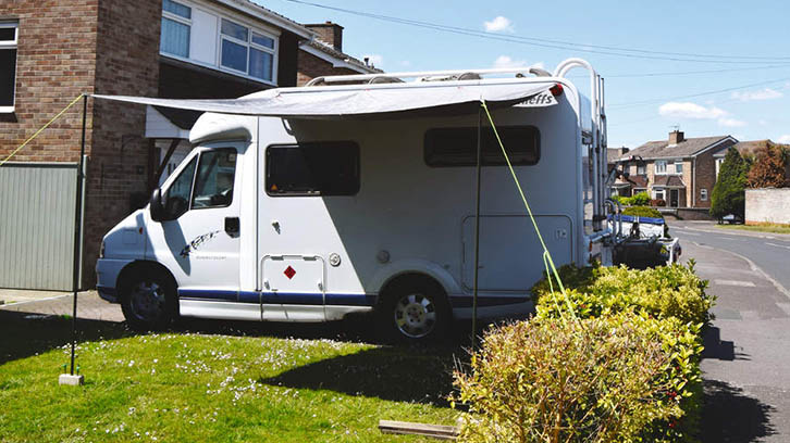Motorhome parked on driveway with an awning