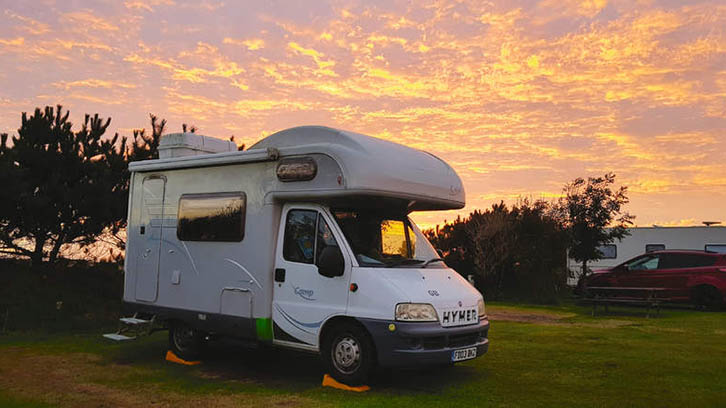 A parked motorhome by the setting sun